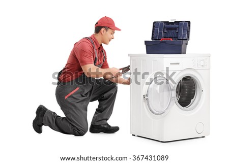 Studio shot of a young male worker repairing a washing machine isolated on white background - stock photo