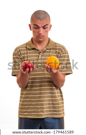 Studio shot of a young man comparing an apple to an orange - stock photo