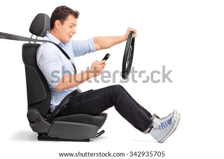 Studio shot of a young man driving a car and looking at his cell phone isolated on white background - stock photo