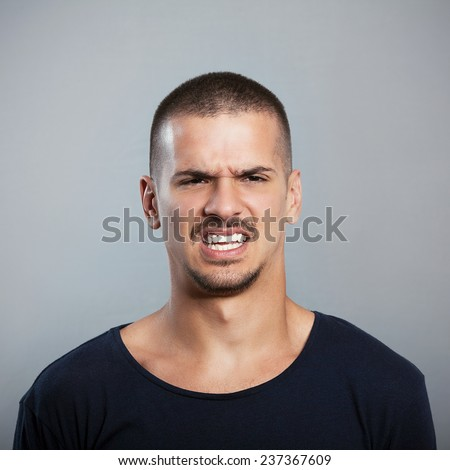 Studio shot of a young man grimacing - stock photo