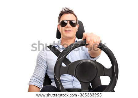 Studio shot of a young man holding a steering wheel and pretending to drive isolated on white background - stock photo