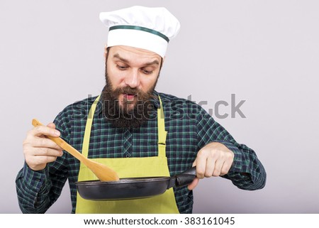 Studio shot of a young man tasting the food with a wooden spoon over gray background