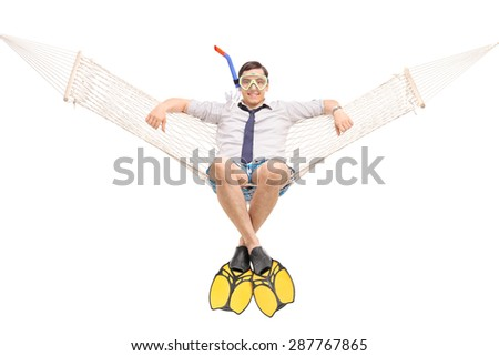 Studio shot of a young man with a snorkel and diving fins lying in a hammock and looking at the camera isolated on white background - stock photo