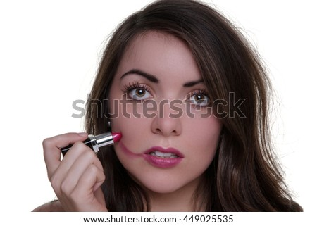 Studio shot of a young model applying lipstick but doing a bad job - stock photo