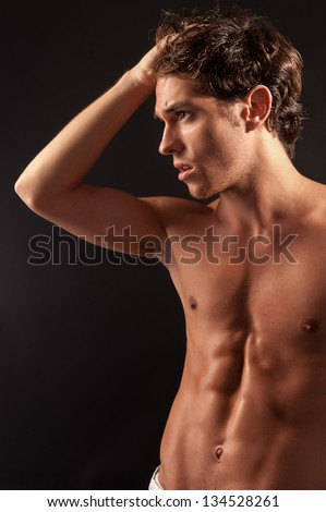 Studio shot of a young sexy male adult looking to the side with one hand on the head. - stock photo