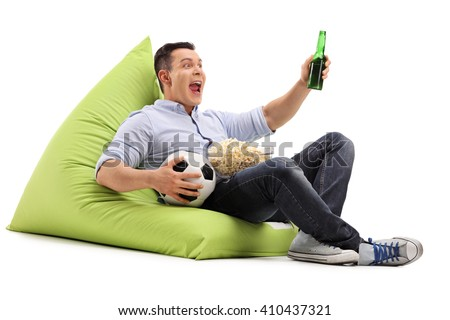 Studio shot of a young soccer fan watching a game with beer and popcorn seated on a beanbag isolated on white background - stock photo