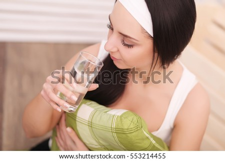 Studio shot of a young woman drinking a glass of water.