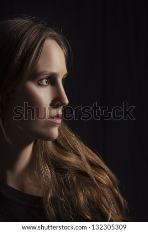 Studio shot of a young woman / girl looking with lowkey lighting. Black background.