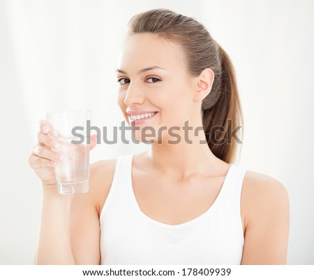 Studio shot of a young woman holding a glass of water. - stock photo