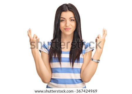 Studio shot of a young woman holding her fingers crossed and looking at the camera isolated on white background - stock photo