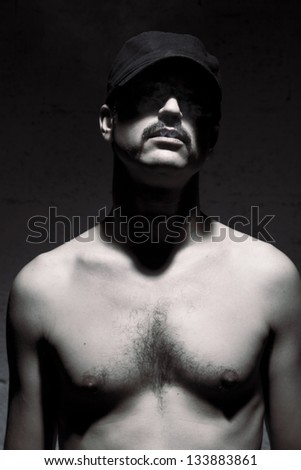 Studio shot of an adult man in his early 30's, standing shirless, smoke coming out of his mouth, in front of the camera on the blurry background of a brick wall. - stock photo