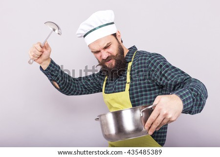 Studio shot of an angry bearded chef holding a ladle and a pot over gray background - stock photo