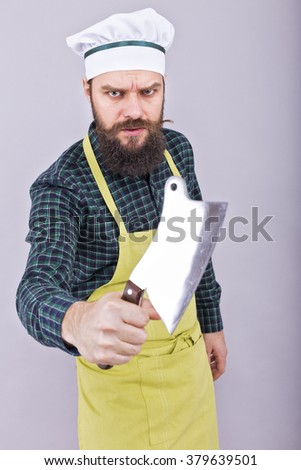 Studio shot of an angry bearded man holding a butcher knife over gray background - stock photo