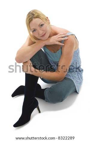 Studio shot of an attractive young woman in her thirties in a relaxed pose wearing long blue boots