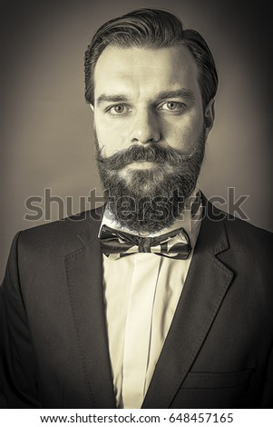 Studio shot of an elegant man with beard and mustache.Gray background