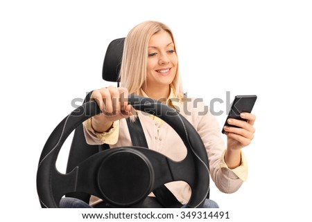 Studio shot of an irresponsible blond woman texting and driving isolated on white background - stock photo