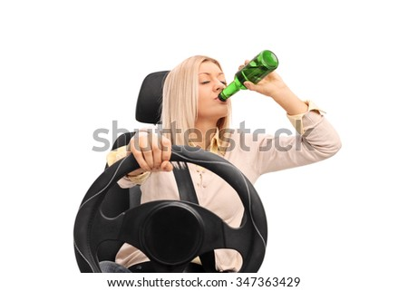 Studio shot of an irresponsible young woman drinking a beer and driving isolated on white background - stock photo