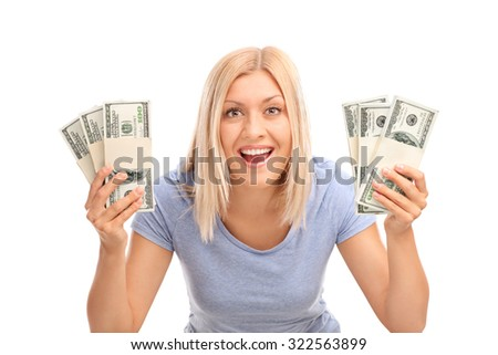 Studio shot of an overjoyed woman holding few stacks of money and looking at the camera isolated on white background - stock photo