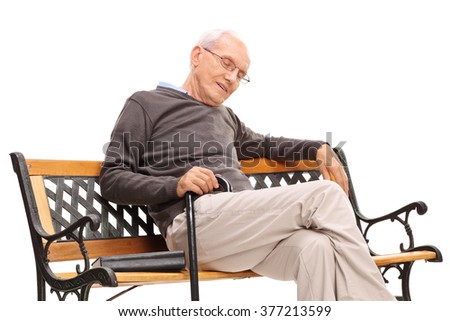 Studio shot of an senior man with cane sleeping on a wooden bench with a book beside him isolated on white background - stock photo