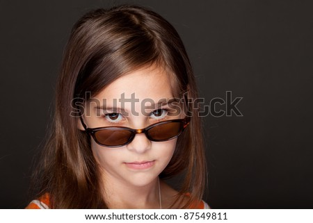 Studio shot of an 8 Year old girl with sunglasses - stock photo
