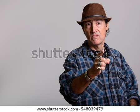 Studio shot of angry mature gangster man pointing finger at camera