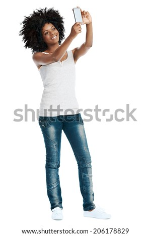Studio shot of attractive african woman with afro taking a picture of herself with her camera phone - stock photo