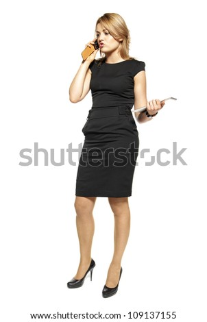 Studio shot of attractive  woman in a black dress. Woman talking on the phone. - stock photo