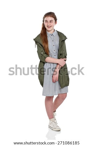 Studio shot of attractive young girl standing over white background and looking away smiling - stock photo
