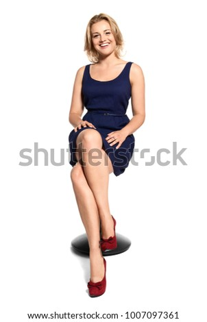 Studio shot of attractive young woman sitting on a stool and smiling to camera. Isolated on white background.