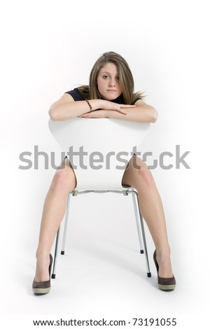 Studio shot of beautiful blonde caucasian girl facing camera on a white chair over white background. - stock photo