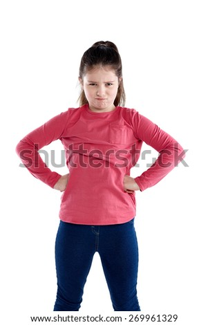 Studio shot of beautiful little girl standing with her hands on hips grimacing against white background. Young girl looking upset. - stock photo