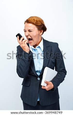 Studio shot of beautiful redheaded business woman. Business woman screaming at mobile phone and holding laptop