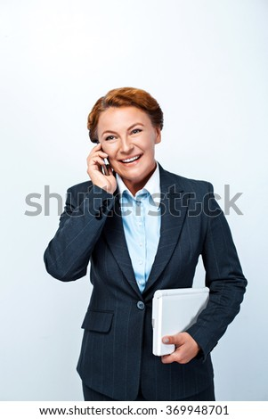 Studio shot of beautiful redheaded business woman. Business woman smiling, using mobile phone and holding laptop
