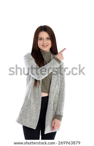 Studio shot of beautiful teenage girl pointing at copyspace while standing on white background - stock photo