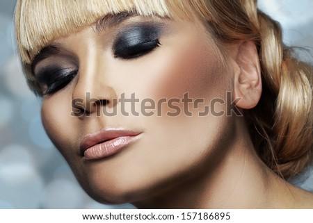 Studio shot of beautiful woman with smokey eyes makeup - stock photo