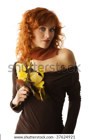 studio shot of beautiful young red haired woman with autumn leaves and brown dark dress - stock photo