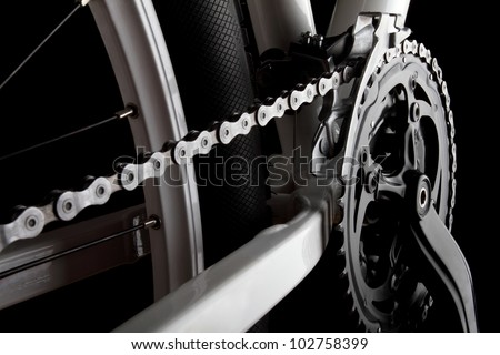 Studio shot of bicycle crank, chain, derailleur and rear wheel. - stock photo