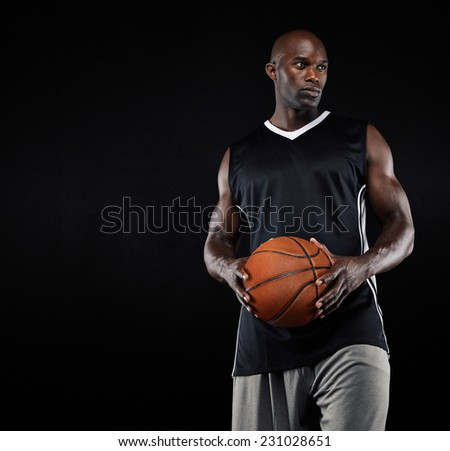 Studio shot of black basketball player with ball looking away against black background. Strong young man with basketball. - stock photo