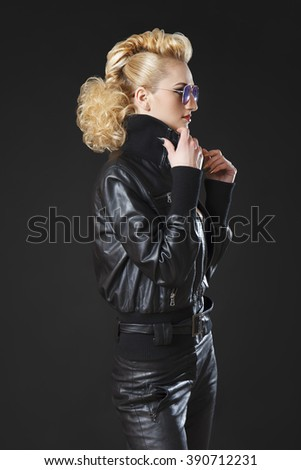 Studio shot of blonde rocker girl wearing black leather jacket and tight leather pants along with sun glasses  - stock photo
