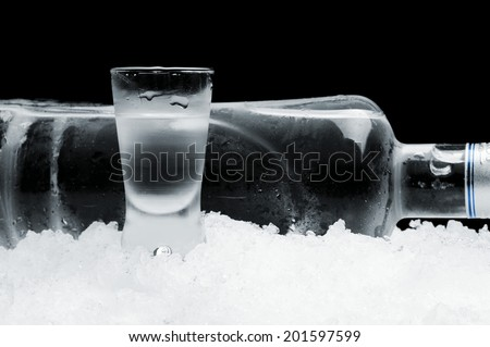 Studio shot of bottle with glass of vodka lying on ice on black background - stock photo