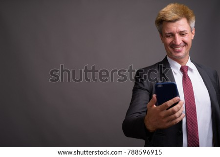 Studio shot of businessman with blond hair against gray background