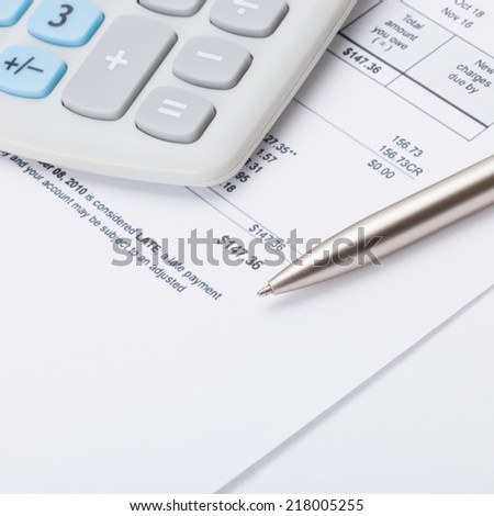 Studio shot of calculator and pen over some receipt - 1 to 1 ratio - stock photo