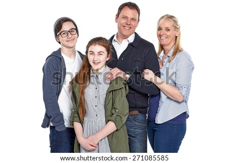 Studio shot of cheerful caucasian family of four standing together over white background - stock photo