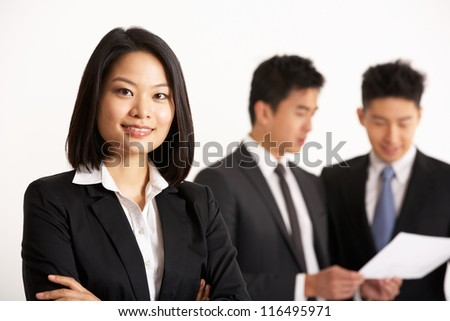 Studio Shot Of Chinese Businesspeople Discussing Document - stock photo