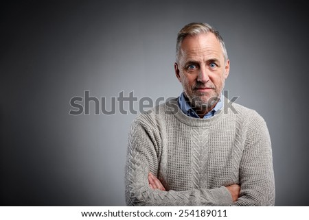 Studio shot of confident mature man standing with his arms crossed against grey background  - Copyspace  - stock photo