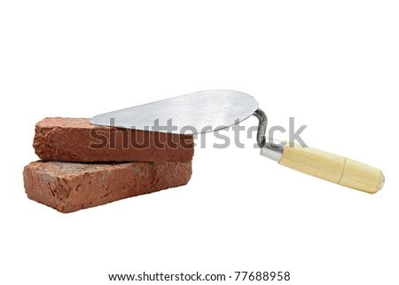 Studio shot of construction lute trowel with red brick - stock photo