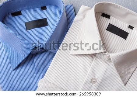 Studio shot of couple of man's shirts on a grey background - stock photo