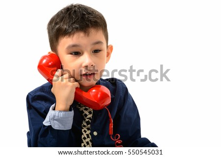 Studio shot of cute boy talking on old telephone and looking down isolated against white background