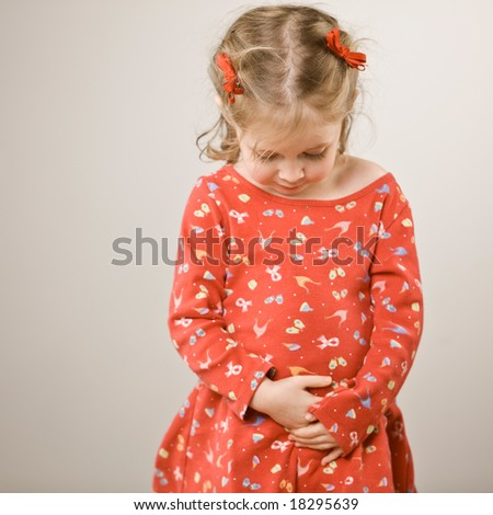 Studio shot of cute girl in festive dress looking down