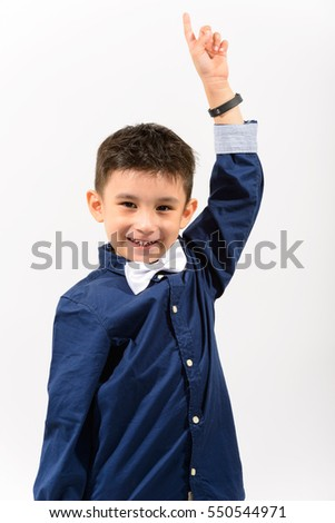 Studio shot of cute happy boy smiling and pointing finger up isolated against white background